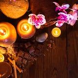 Badekurortkonzept mit Schokolade und Kerzen auf einem hölzernen Hintergrund lizenzfreies stockbild