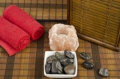 Badekurortkonzept mit Steinen, Salz und Tüchern Stockbilder
