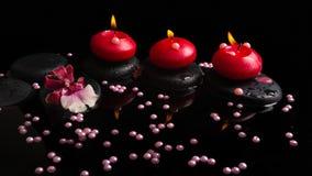Badekurortkonzept von roten Kerzen, Zensteine mit Tropfen, Orchidee Lizenzfreie Stockfotografie