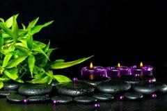 Badekurortkonzept von Zenbasaltsteinen mit Tropfen, lila Kerzen, Perle Lizenzfreie Stockfotos