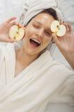 Badekurortmädchen, das den Spaß blinzelt und hält einen Apfel hat Lizenzfreies Stockfoto