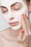 Badekurortmädchen, das Gesichtsmaske anwendet Lizenzfreie Stockfotos