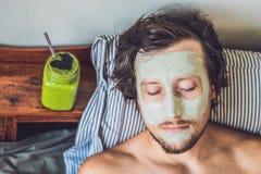 Badekurortmann, der grüne Lehm im Gesichtmaske anwendet Schönheits-Behandlungen Frischer grüner Smoothie mit Banane und Spinat mi lizenzfreie stockbilder