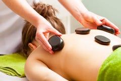 Badekurortsalon. Frau, die Warmsteinmassage habend sich entspannt. Bodycare. Lizenzfreies Stockfoto