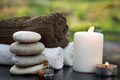 Badekurortstillleben mit Tüchern, einer brennenden Kerze, Badeöl und Massagesteinen gegen den Hintergrund eines grünen Gartens im stockfotos