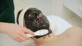 Badekurorttherapie f?r die gutaussehenden M?nner, die Gesichtsmaske empfangen Aufnahme eines Cosmetologist stock video