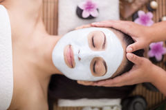 Badekurorttherapie für die junge Frau, die Gesichtsmaske am Schönheitssalon hat Stockbild