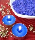 Badekurortwesensmerkmale (blaues Salz, Kerze und Blume) Stockfotos