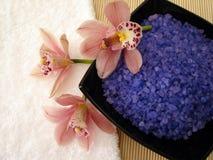 Badekurortwesensmerkmale (violettes Salz, weißes Tuch und rosafarbene Orchideen) Stockfotos