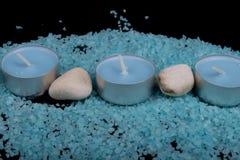 Badekurortzusammensetzung im Blau, in den Kerzen und im blauen Seesalz mit Steinen Stockfotografie