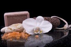 Badekurortzusammensetzung mit Blume und Seesalz und Steine auf schwarzem BAC Lizenzfreies Stockfoto