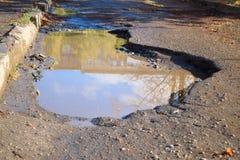 Baden asfalterade vägen med en stor grop Royaltyfri Foto