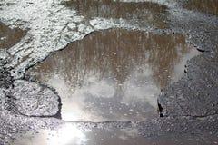 Baden asfalterade vägen med en stor grop som fylldes med vatten Farlig förstörd roadbed arkivfoton