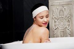 Baden der Frau, die im Bad sich entspannt Stockbild