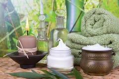 Baden von Salz- und Massageölen mit einem Stapel Tüchern lizenzfreie stockfotos