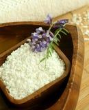 Badesalz in der hölzernen Schüssel und in den Blumen. Lizenzfreies Stockfoto