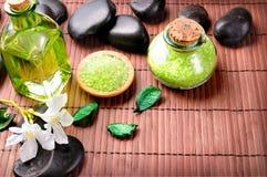 Badesalz und Öl mit Blumen und Draufsicht der Steine Stockbilder