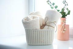 Badetücher im Korb auf leerem Kopienraum des Fensterbretts lizenzfreies stockfoto