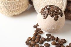 Badet bombarderar med kaffekorn på en vit Arkivfoton