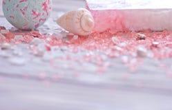 Badet bombarderar, snäckskal, den handgjorda tvålstången och rosa färgbrunnsorten som är salta för kroppomsorg Mjuk fokus på förg Royaltyfria Foton