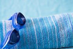 Badetuch mit Schwimmenschutzbrillen Stockfotos