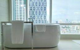 Badewanne am Fenster mit Stadtansicht Stockfotografie