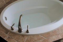 Badewanne gefüllt mit Wasser in einem Badezimmer Lizenzfreie Stockfotos