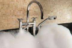Badewanne voll des Schaum- und Chromhahns Lizenzfreie Stockbilder