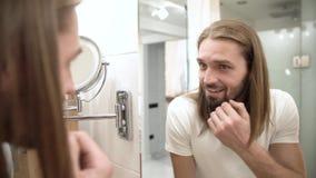 Badezimmer Mann, der im Spiegel und in rührendem Gesicht schaut stock video