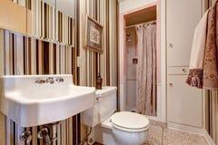 Badezimmer mit Braun abgestreifter Tapete Stockfoto