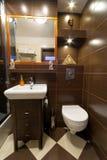 Badezimmerinnenraum mit braunen Fliesen Stockbild