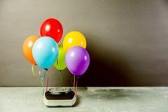 Badezimmerwaagen mit bunten Ballonen Abnehmen des Konzeptes lizenzfreies stockfoto