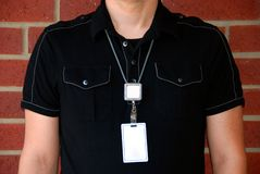 Badge - 2. Man wearing a blank ID badge in front of a brick wall Royalty Free Stock Photography
