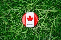 badge avec la feuille d'érable canadienne blanche rouge de drapeau se situant dans l'herbe sur le fond vert de nature de forêt de Photos stock