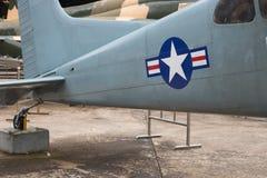 Badge mit einem Adler, der eine Klinge, ein Schild und ein Militärflugzeug anhält Lizenzfreie Stockbilder