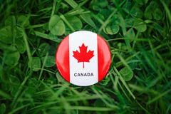 Badge with red white canadian flag maple leaf lying in grass on green forest nature background outside, Canada day. Macro closeup shot of round circle badge with Royalty Free Stock Images
