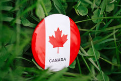 Badge with red white canadian flag maple leaf lying in grass on green forest nature background outside, Canada day. Macro closeup shot of round circle badge with Royalty Free Stock Photos