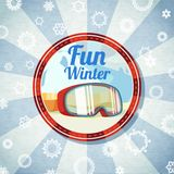 Badge with snowboarders or skiers goggles, -Fun. Badge with snowboarders or skiers goggles, with -Fun Winter- slogan. Retro stylized background on bright Royalty Free Stock Image