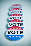 Badges for the United States election. Some aligned badges with the word vote written in it, for the United States election, with a slight vignette added Royalty Free Stock Photography