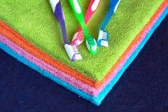 Badhanddoeken van verschillende kleuren en tandenborstelsclose-up stock afbeelding