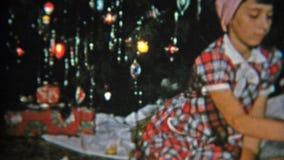 1951 : Badine des cadeaux de Noël d'ouverture devant l'arbre de fête NEWARK, NEW JERSEY banque de vidéos