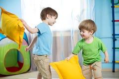 Badine des garçons jouant avec des oreillers Images stock