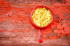 Badine des macaronis de fromage dans le pot d'argile sur la table rustique Photographie stock