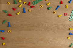 Badine la frontière d'outils de jouets de construction Vis et écrous colorés sur le fond en bois Vue supérieure Configuration pla photo libre de droits