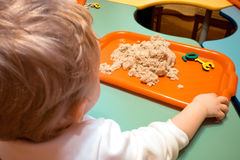 Badine la leçon se développante d'école bleue du ` s de bébé garçon se reposant sur une chaise et étend le sable cosmique sous un Images stock