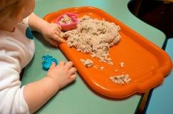 Badine la leçon se développante d'école bleue du ` s de bébé garçon se reposant sur une chaise et étend le sable cosmique sous un Photos libres de droits