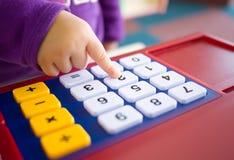 Badine le doigt appuyant la calculatrice de jouet Photographie stock