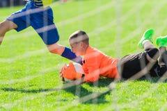 Badine le football du football - les joueurs d'enfants sont assortis sur le terrain de football Images libres de droits