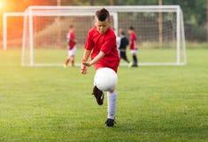 Badine le football du football - les joueurs d'enfants sont assortis sur le terrain de football Photos libres de droits