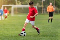 Badine le football du football - les joueurs d'enfants sont assortis sur le terrain de football Photos stock